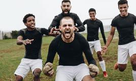 Portiere che fa uno scorrevole del ginocchio nell'eccitazione dopo la conquista della partita Compagni di squadra di calcio che c immagine stock