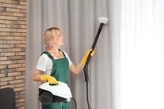 Portiere femminile che rimuove polvere dalla tenda con il pulitore a vapore immagine stock