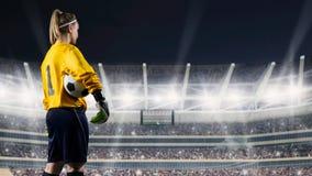Portiere femminile che sta con la palla contro lo stadio ammucchiato alla notte immagine stock libera da diritti