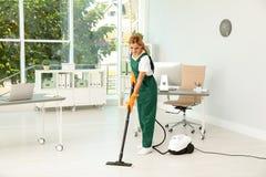 Portiere femminile nel pavimento uniforme di pulizia immagini stock
