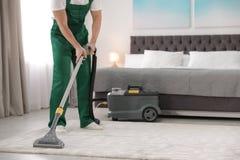 Portiere professionista che rimuove sporcizia dal tappeto con l'aspirapolvere in camera da letto, primo piano fotografia stock