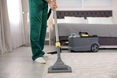 Portiere professionista che rimuove sporcizia dal tappeto con l'aspirapolvere in camera da letto Spazio per testo fotografia stock