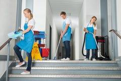 Portiers nettoyant le couloir avec des équipements de nettoyage photographie stock libre de droits