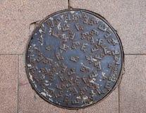 Portilla de la alcantarilla del metal en el pavimento Fotos de archivo