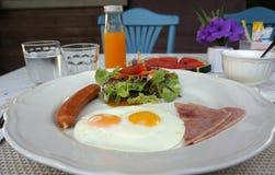 Portion américaine de petit déjeuner avec l'oeuf au plat, le jambon, la saucisse et la salade images libres de droits