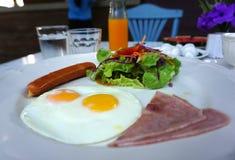 Portion américaine de petit déjeuner avec l'oeuf au plat, le jambon, la saucisse et la salade photo stock