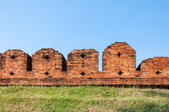 A portion of the ancient fortified city wall built of brick with cross bow cutouts and crenelations Stock Photo