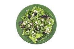 Portion av ny grekisk sallad med lövrika gräsplaner, örter, arugulan feta, oliv, feta och oliv på en grön olate, vit Arkivbild