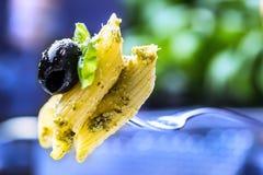 Portion av pennepasta på en gaffel med basilikasidor och svart oliv Royaltyfri Fotografi