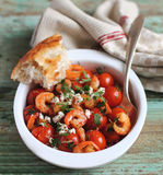 Portion of baked cherry tomatoes and roasted shrimps Stock Photo