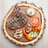 Portion of BBQ t-bone steak with sauce and grilled vegetables. Portion of BBQ t-bone steak served on wooden board with rosemary, mustard sauce and grilled stock photography