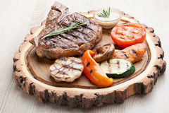 Portion of BBQ t-bone steak with  sauce  and grilled vegetables Stock Photos
