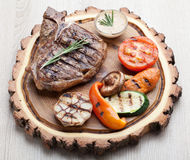Portion of BBQ t-bone steak with  sauce  and grilled vegetables Royalty Free Stock Photos