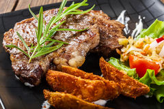 Portion of beef steak served with roast potatoes Stock Image