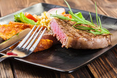 Portion of beef steak served with roast potatoes Royalty Free Stock Photos