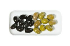 Portion of black and green giant olives in a bawl. Isolated on white background royalty free stock images