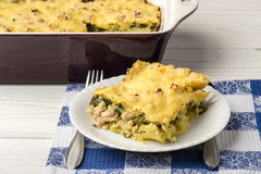 Portion of casserole with spinach, chicken and potatoes on the wooden background. Royalty Free Stock Photo