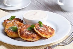 Portion cheese pancakes on a white plate with sour cream Royalty Free Stock Photo