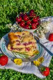 Portion of cherry cake with ripe strawberries around and other cherries in bowl Royalty Free Stock Photos