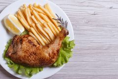Portion of chicken legs, french fries on a white plate. Royalty Free Stock Images