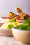 Portion of chicken legs on plate behind potatoes and salad Royalty Free Stock Images