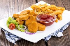 Portion of Chicken Nuggets. Portion of golden Chicken Nuggets with some french fries Royalty Free Stock Image