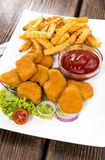 Portion of Chicken Nuggets. Portion of golden Chicken Nuggets with some french fries Royalty Free Stock Photos