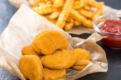 Portion of Chicken Nuggets. Portion of golden Chicken Nuggets with some french fries Stock Images