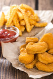 Portion of Chicken Nuggets. Portion of golden Chicken Nuggets with some french fries Royalty Free Stock Photography