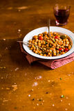 Portion of chickpea stew with cherry tomatoes, roasted chicken, capers and lemon zest in plate on a wooden table Royalty Free Stock Photography