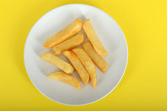Portion of Chips. On a plate against a yellow background Royalty Free Stock Image