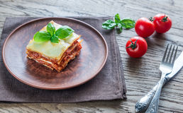 Portion of classic lasagne. With fresh basil on the plate stock image
