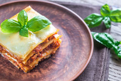 Portion of classic lasagne. With fresh basil on the plate royalty free stock photos