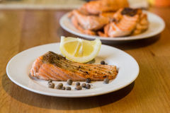 Portion of cooked salmon fillet with lemon slice on white plate. With fork and knife on wooden table Stock Image