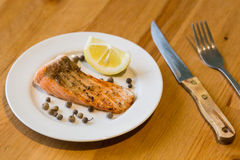 Portion of cooked salmon fillet with lemon slice on white plate. With fork and knife on wooden table Royalty Free Stock Photo