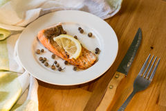 Portion of cooked salmon fillet with lemon slice on white plate. With fork and knife on wooden table Royalty Free Stock Images