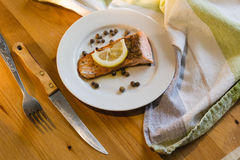 Portion of cooked salmon fillet with lemon slice on white plate. With fork and knife on wooden table Stock Photography