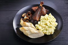 A portion of Coq Au Vin. Classic French chicken stew served on black plate with potato puree and french bread, horizontal view from above, close-up Stock Image