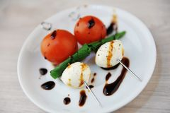 Portion créative de salade caprese Tomate entière, boule de fromage de mozzarella, feuille verte de basilic sur des brochettes Sa photo stock