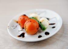 Portion créative de salade caprese Tomate entière, boule de fromage de mozzarella, feuille verte de basilic sur des brochettes Sa photo libre de droits