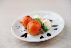 Portion créative de salade caprese Tomate entière, boule de fromage de mozzarella, feuille verte de basilic sur des brochettes Sa photographie stock libre de droits