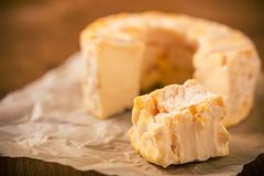 Portion cut from whole golden camembert cheese on crumpled paper sheet Stock Photography