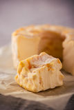 Portion cut from whole golden camembert cheese on grey board Royalty Free Stock Photography