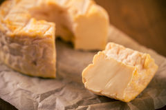 Portion cut from whole golden camembert cheese on paper sheet Royalty Free Stock Image