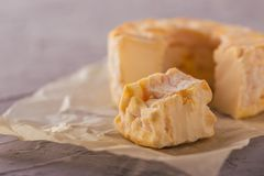 Portion cut from whole golden camembert on grey board Royalty Free Stock Image