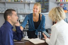 Portion de femme derrière la barre en café photographie stock libre de droits