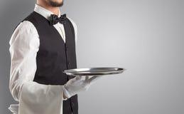 Portion de serveur avec les gants blancs et le plateau en acier photographie stock libre de droits