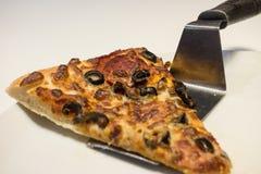 Portion de tranche de pizza avec la spatule du plat blanc Photographie stock
