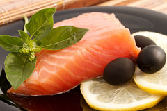 The portion of delicious salmon with basil, lemon and olives Stock Photos