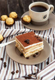 Portion of delicious tiramisu cake. And coffee cup on the background Stock Photo